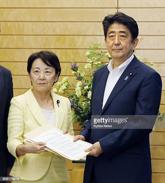 Eriko Yamatani of the Liberal Democratic Party hands a written proposal to Japanese Prime Minister Shinzo Abe in Tokyo on Sept. 16 for fresh...