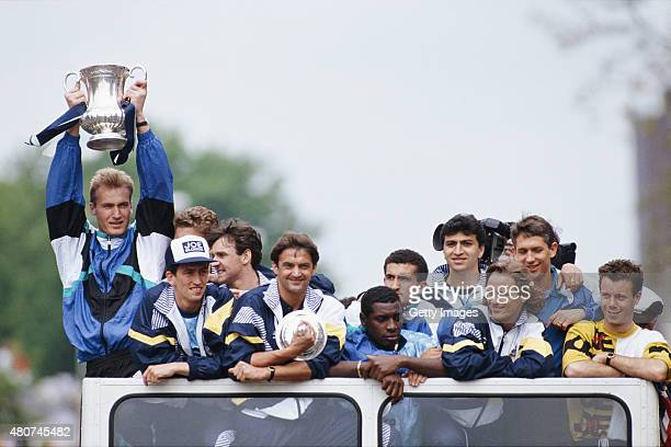 ErikThorstvedt of Tottenham Hotspur holds aloft the trophy as his team mates including Gary Mabbutt and Gary Lineker look on during their homecoming...