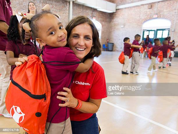 Erin Bradshaw Save the Children Sr Director for Emergency Preparedness gets a hug from a child who received a backpack with disaster supplies to...