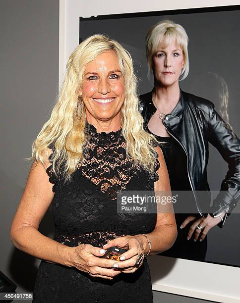 Erin Brockovich poses for a photo next to her portrait at The Boomer List Photographs by Timothy GreenfieldSanders exhibit at The Newseum on October...