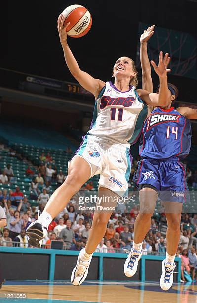 Erin Buescher of the Charlotte Sting goes to the basket past Deanna Nolan of the Detoit Shock during the game on July 27 2002 at Charlotte Coliseum...