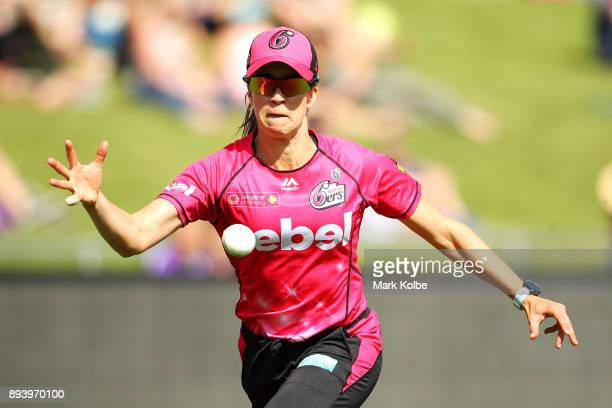 Erin Burns of the Sixers stops a ball in the outfield during the Women's Big Bash League match between the Hobart Hurricanes and the Sydney Sixers at...