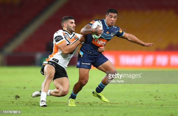 Erin Clark of the Titans is tackled by Adam Doueihi of the Tigers during the round four NRL match between the Gold Coast Titans and the Wests Tigers...