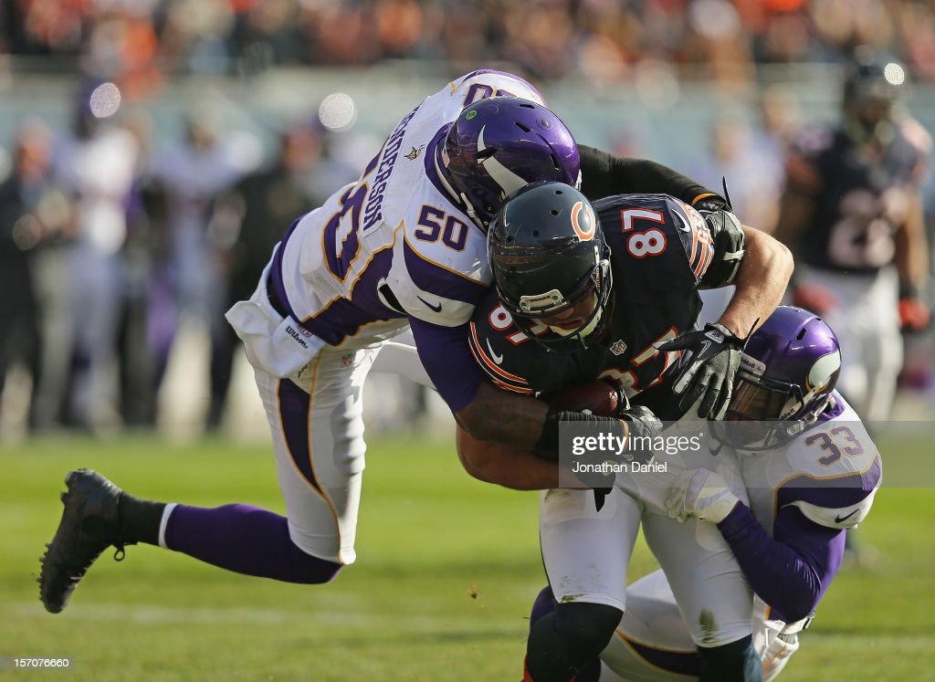 Erin Henderson #50 and Jamarca Sanford #33 of the Minnesota Vikings tackle Kellen Davis #87 of the Chicago Bears at Soldier Field on November 25, 2012 in Chicago, Illinois. The Bears defeated the Vikings 28-10.