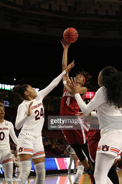 Erin Howard forward of Auburn defends as Cierra Johnson guard of Alabama takes a shot during the SEC Women's basketball tournament between the...