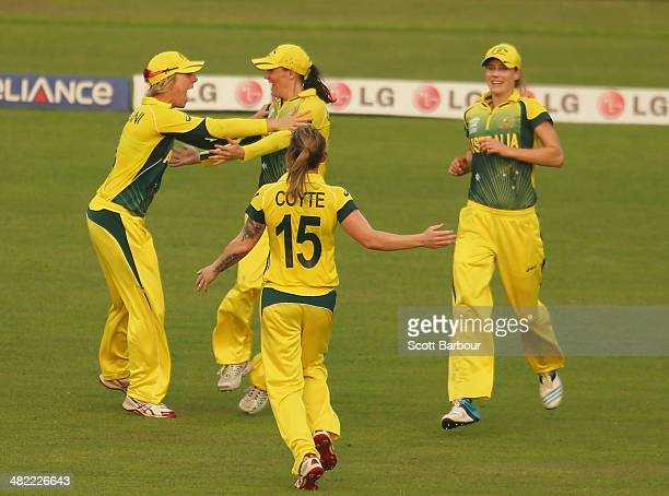 Erin Osborne of Australia is congratulated by her teammates after taking a catch on the boundary to dismiss Deandra Dottin of the West Indies during...