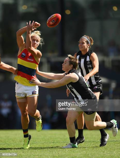 Erin Phillips of the Crows handballs whilst being tackled during the round seven AFLW match between the Collingwood Magpies and the Adelaide Crows at...