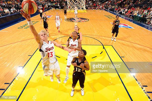 Erin Phillips of the Indiana Fever lays the ball up over Ivory Latta of the Tulsa Shock at Conseco Fieldhouse on June 14 2011 in Indianapolis Indiana...