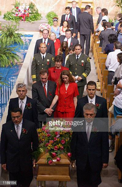 Erin Runnion, front in red is accompanied by her husband Ken Donnelly as they follow the casket holding her 5 year old daughter Samantha Runnion at...
