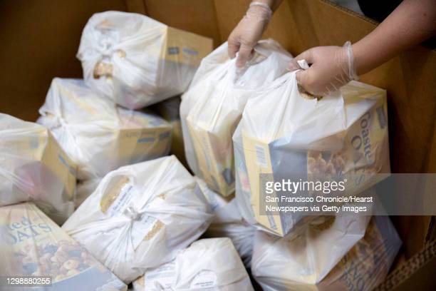 Erin Suth packs the box with food bags at the Alameda County Community Food Bank that will be distributed to furloughed government employees on...