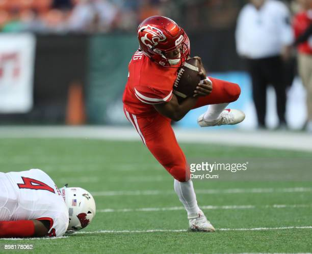 Eriq King of the Houston Cougars stays out of the reach of Mike Bell of the Fresno State Bulldogs during the third quarter of the Hawaii Bowl at...