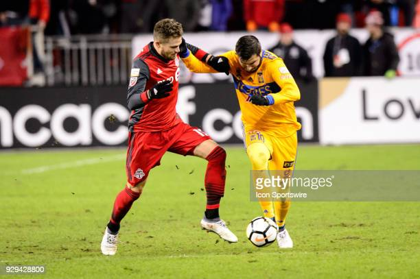 Eriq Zavaleta of Toronto FC attempts to stop AndréPierre Gignac of Tigres UANL during the CONCACAF Champions League Quarterfinal match between...