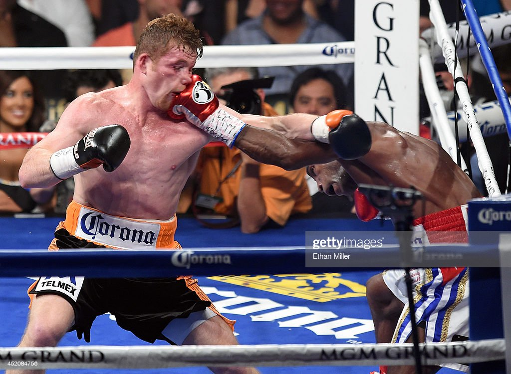 Erislandy Lara (R) hits Canelo Alvarez in the fourth round of their junior middleweight bout at the MGM Grand Garden Arena on July 12, 2014 in Las Vegas, Nevada. Alvarez won in a split decision.