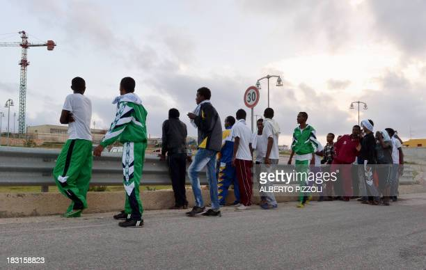 Erithrean migrants walk walk near the Lampedusa airport on October 5, 2013 after a boat with migrants sank killing more than hundred people. Italy...