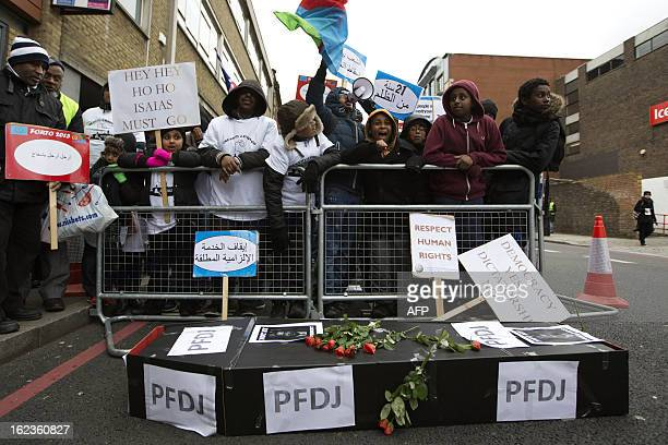 Eritrean demonstrators shout slogans as they stand behind a mock coffin during a protest outside the Embassy of Eritrea in central London on February...