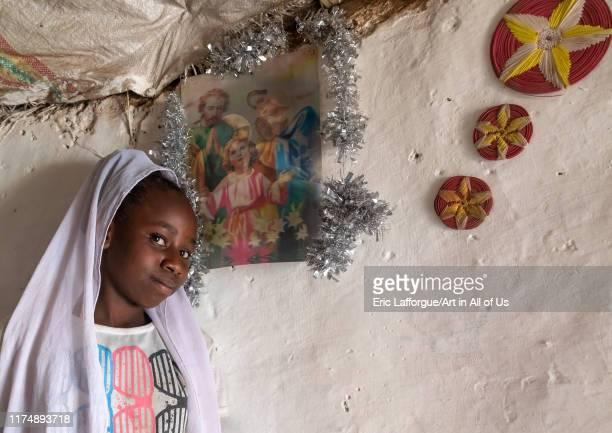 Eritrean Kunama tribe teenage girl in front of a religious poster GashBarka Barentu Eritrea on August 20 2019 in Barentu Eritrea