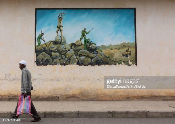 Eritrean man pssing in front of a propaganda mural about the war with ethiopia SemienKeihBahri Keren Eritrea on August 20 2019 in Keren Eritrea