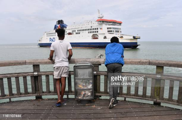 Eritrean migrants look at a ferry boat arriving at Calais' harbour from Great Britain on August 04, 2019 in Calais.