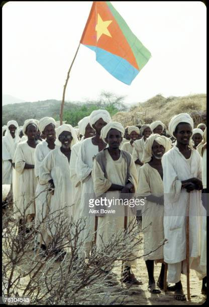 Eritrean nomads attend an EPLF recruitment drive at a desert wadi in northern Eritrea 20th June 1978 An Eritrean flag flies in the background