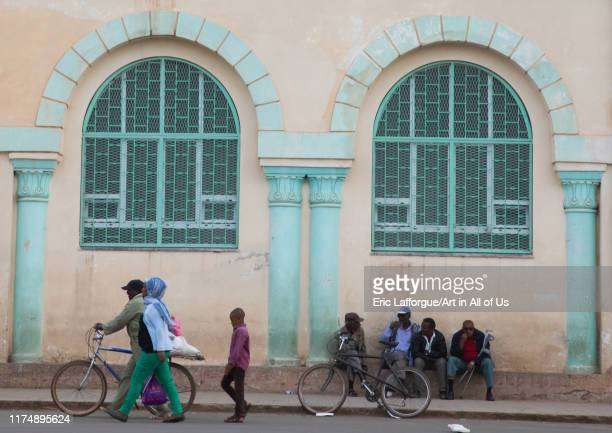 Eritrean people in front of a building from the italian colonial times near the mosque, Central region, Asmara, Eritrea on August 21, 2019 in Asmara,...