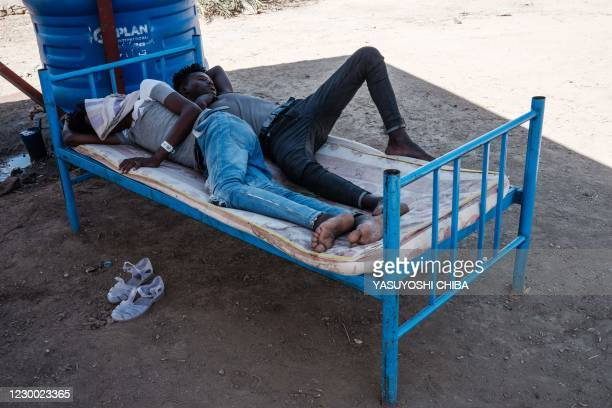Eritrean refugees who fled Ethiopia's Tigray conflict, rest on a bed at the Border Reception Centre in Hamdayit, eastern Sudan, on December 8, 2020....