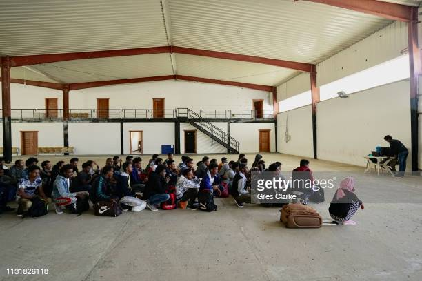 Eritrean, Sudanese and Ethiopian migrants waiting in a detention center to registered by a UNCHR staff member before being transferred to 'gathering...