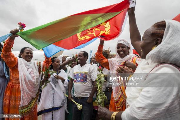 Eritrean women hold up the flag of Eritrea on July 18 to welcome passengers of the flight from Ethiopian capital Addis Ababa upon their arrival at...