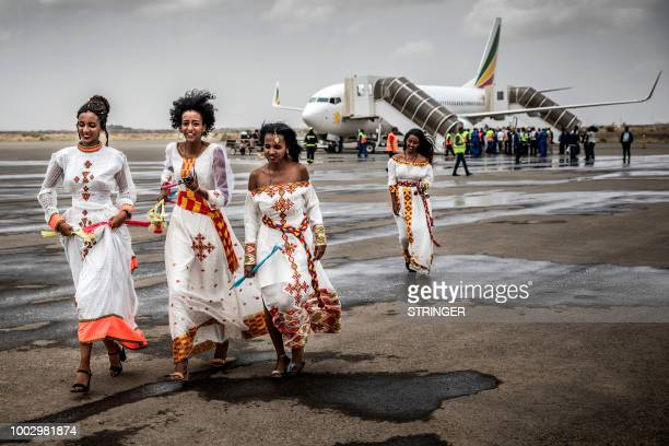 Eritrean women run on the tarmac to welcome passengers of the flight from Ethiopian capital Addis Ababa upon the arrival at Asmara International...