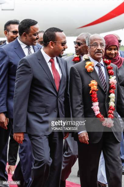 Eritrea's Foreign minister Osman Saleh Mohammed walks with Ethiopia's Prime Minister Abiy Ahmed as Eritrea's delegation arrives for peace talks with...