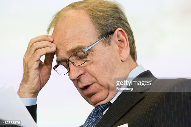 Erkki Liikanen governor of the Bank of Finland looks at documents as he addresses the European Central Bank and its watchers conference in Frankfurt...