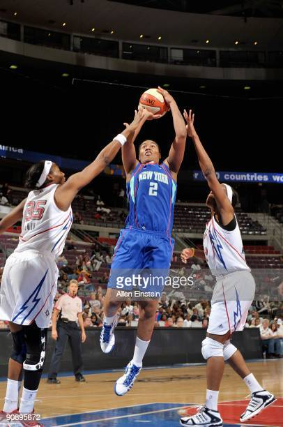 Erlana Larkins of the New York Liberty goes up for a shot over Cheryl Ford and Taj McWilliams of the Detroit Shock during the WNBA game on September...
