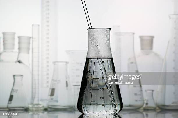 erlenmeyer flask with laboratory glassware in the background - volume fluid capacity stock pictures, royalty-free photos & images