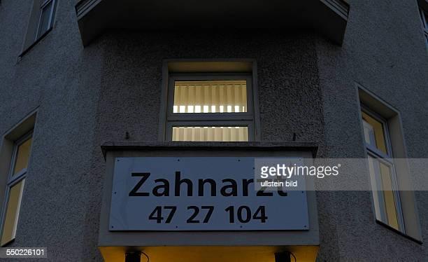Erleuchtete Fenster einer Zahnarztpraxis an der Schönhauser Allee in Berlin