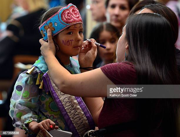 Erlidawn Roy representing the Meskwaki Ojibwe Laguna Pueblo and the Isleta Pueblo tribes writes a message I am not your mascot on the face of LacyJay...