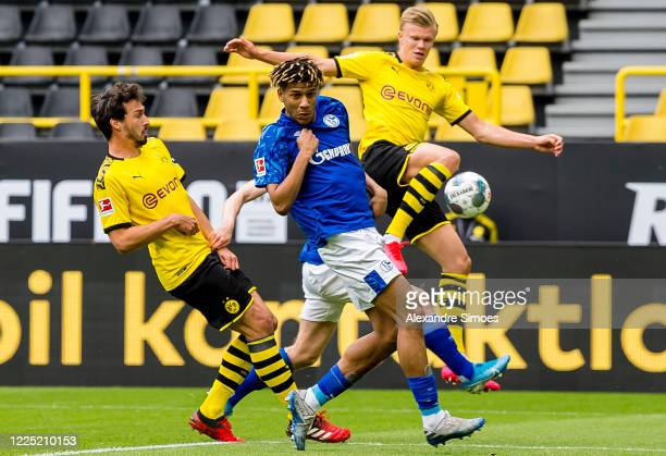 Erling Haaland of Borussia Dortmund and Mats Hummels of Borussia Dortmund are challenged by Jean-Clair Todibo of FC Schalke 04 during the Bundesliga...
