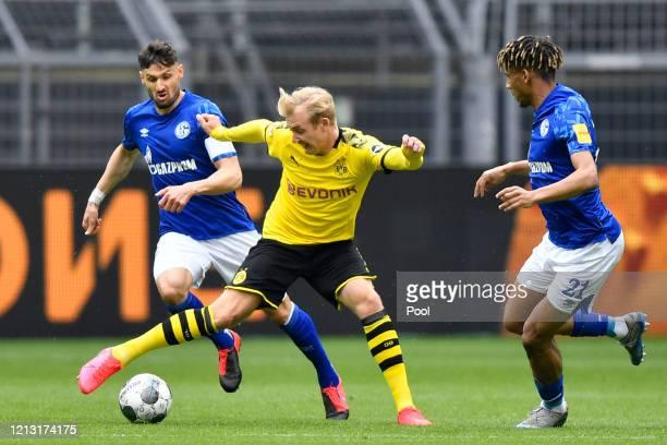 Erling Haaland of Borussia Dortmund battles for the ball with Daniel Caligiuri and JeanClair Todibo of FC Schalke 04 during the Bundesliga match...