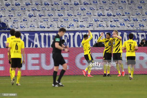 Erling Haaland of Borussia Dortmund celebrates with teammates Jadon Sancho and Jude Bellingham after scoring his team's fourth goal during the...