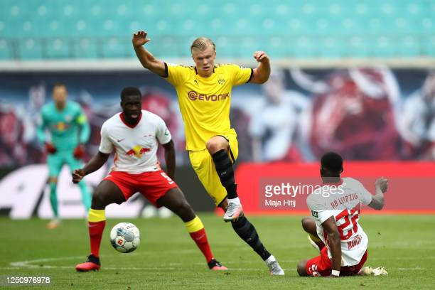Erling Haaland of Borussia Dortmund is challenged by Dayot Upamecano and Nordi Mukiele of RB Leipzig during the Bundesliga match between RB Leipzig...