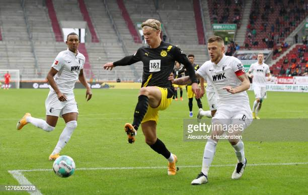 Erling Haaland of Borussia Dortmund is put under pressure by Jeffrey Gouweleeuw of FC Augsburg during the Bundesliga match between FC Augsburg and...