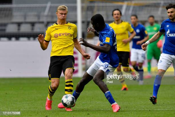 Erling Haaland of Borussia Dortmund is tackled by Salif Sane of FC Schalke 04 during the Bundesliga match between Borussia Dortmund and FC Schalke 04...