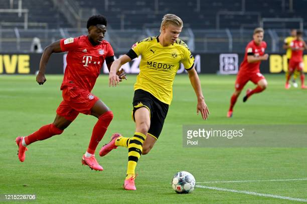 Erling Haaland of Borussia Dortmund runs with the ball past Alphonso Davies of Bayern Munich during the Bundesliga match between Borussia Dortmund...