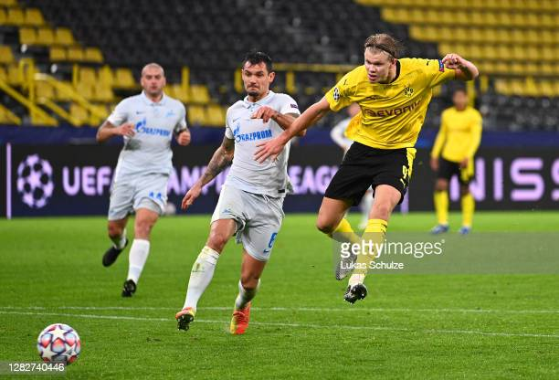 Erling Haaland of Borussia Dortmund scores his sides second goal whilst under pressure from Dejan Lovren of Zenit St. Petersburg during the UEFA...