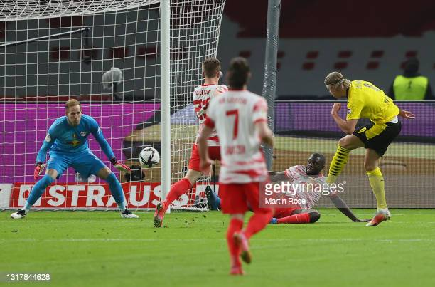 Erling Haaland of Borussia Dortmund scores his team's second goal against goalkeeper Peter Gulacsi and under pressure from Dayot Upamecano and Marcel...