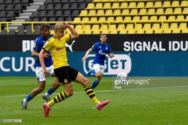 Erling Haaland of Borussia Dortmund shoots and scores his team's first goal during the Bundesliga match between Borussia Dortmund and FC Schalke 04...