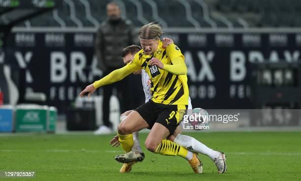 Erling Haaland of Dortmund is challenged by Matthias Ginter of Moenchengladbach during the Bundesliga match between Borussia Moenchengladbach and...