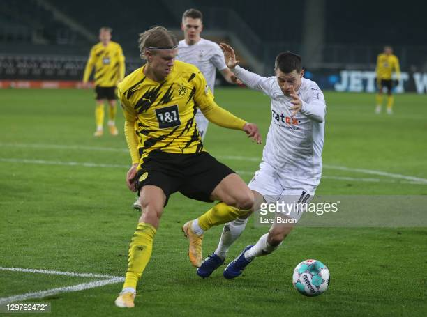 Erling Haaland of Dortmund is challenged by Stefan Lainer of Moenchengladbach during the Bundesliga match between Borussia Moenchengladbach and...