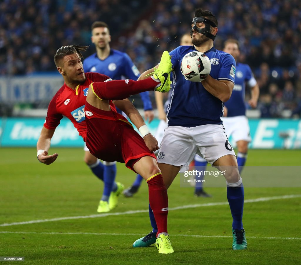 Ermin Bicakcic of Hoffenheim is challenged by Sead Kolasinac of Schalke during the Bundesliga match between FC Schalke 04 and TSG 1899 Hoffenheim at Veltins-Arena on February 26, 2017 in Gelsenkirchen, Germany.