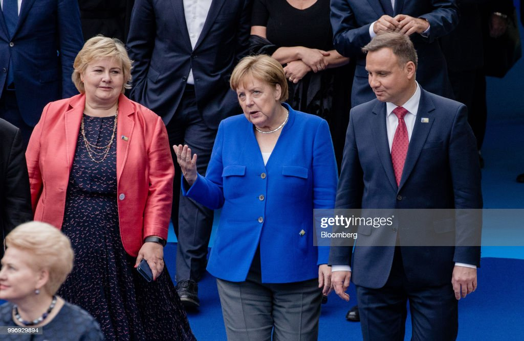 Erna Solberg, Norway's prime minister, left, Angela Merkel, Germany's chancellor, center, and Andrzej Duda, Poland's president, arrive for a working dinner during the North Atlantic Treaty Organization (NATO) summit at the museum of art and history in Cinquantenaire park in Brussels, Belgium, on Wednesday, July 11, 2018. President Donald Trump opened up another front in his tussle with allies on his arrival at NATOs annual summit, targeting Germany over its support for the Nord Stream 2 gas pipeline from Russia. Photographer: Marlene Awaad/Bloomberg via Getty Images