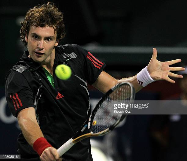 Ernest Gulbis of Latvia hits a backhand in his second round match against Mardy Fish of the United States during day three of the Rakuten Open at...