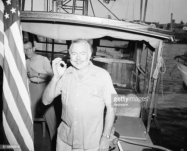 Ernest Hemingway, aboard his boat Pilar, indicates the size of his catch with a big goose egg after the first day of a three-day international...